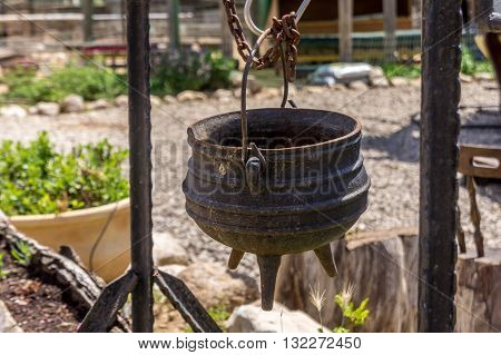 Old cast iron pot on a three legs for cooking is suspended on the hook on the farm in the desert Israel