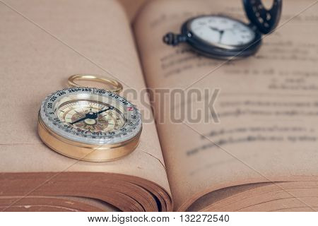 Vintage Compass on open old book and pocket watch