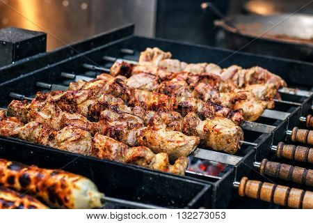 Grilling marinated shashlik preparing on a barbecue grill over charcoal. Shashlik is a form of Shish kebab popular in Eastern Europe. Shashlyk (meaning skewered meat) was originally made of lamb.