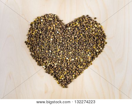 Heart shaped from raw dry brown lentils in cup, top view, center composition, food preparation, copy space, healthy lifestyle, eating legumes