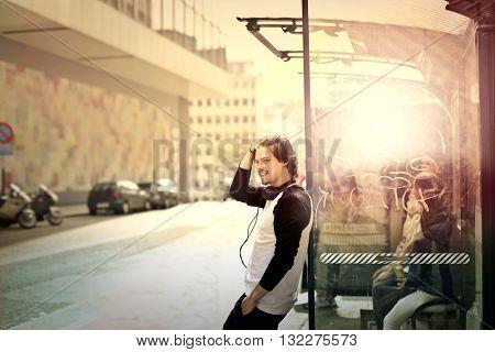 Young man waiting at the bus stop