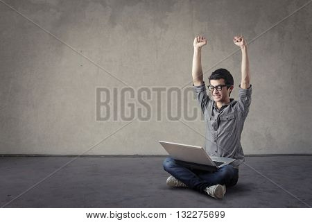 Jubilant young student with laptop