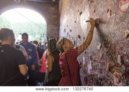 Verona Italy September 26 2015: Young girl write a letter to Juliet on the wall in the passage to Juliet's house in Verona Italy