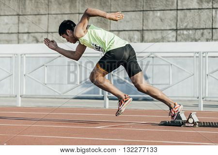 Chelyabinsk Russia - May 24 2016: male athlete starts from starting blocks on a distance of 400 meters during UrFO Championship in athletics