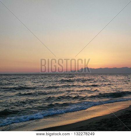 Tramonto in spiaggia con Sole che cade nel mare