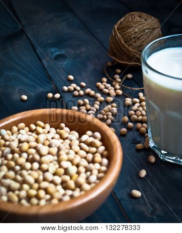Glass of soy milk and full bowl of soy beans on wooden background