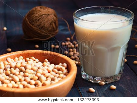 Glass of soy milk and full bowl of soy beans on wooden background. Non-dairy milk. Healthy concept