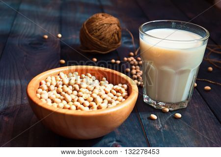 Glass of soy milk and full beige bowl of soy beans on wooden background