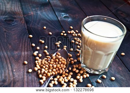 Glass of soy milk and soy beans on wooden background. Rustic style