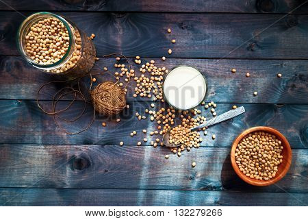 Glass of soy milk and dried soy beans in the spoon bowl and jar as food background