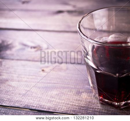 Unfinished glass of red wine on rustic wooden bar table