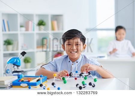 Portrait of Vietnamese schoolboy sitting in chemistry class