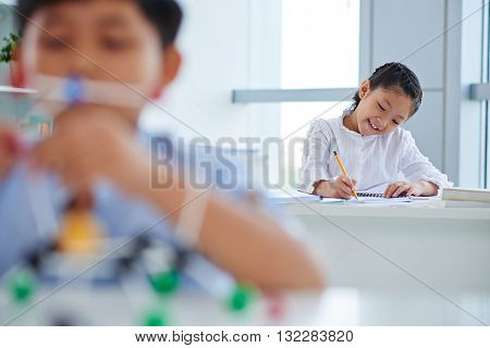 Schoolgirl writing essay in class, her classmate in foreground