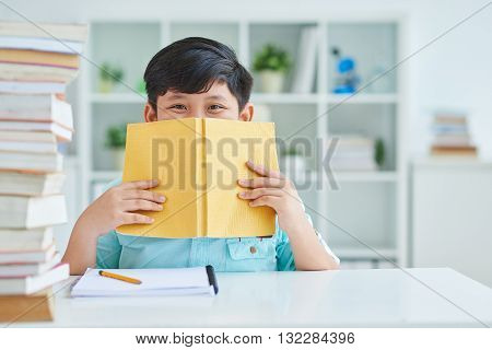 Cheerful schoolboy hiding his smile behind book