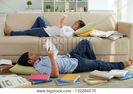 Children lying on sofa and floor and reading different books
