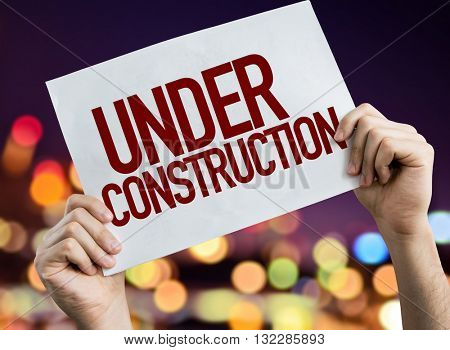 Under Construction placard with night lights on background