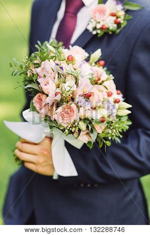 Male hands holding beautiful bridal bouquet with roses and red berries in summer
