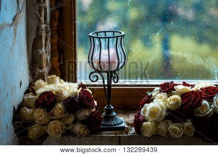 Old dirty window with two flower bunches and candlestick on grunge cement windowsill on blurred glass background