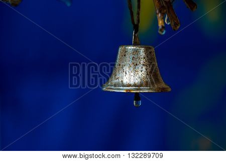 Rusty bell wet with drop of rain on clapper hangs on tree on blue background