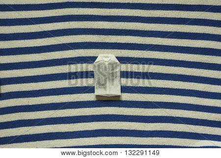 Tea bag on blue white textile close up