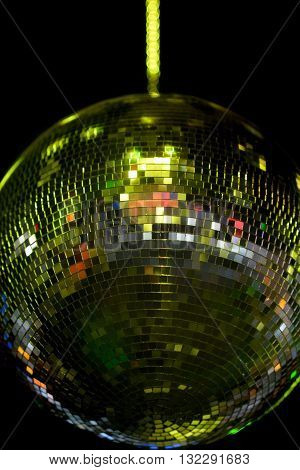 Disco mirror ball yellow lighting on dark background