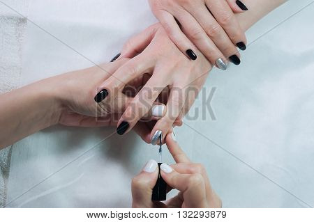 Nails transparent cover is a close-up in a beauty salon. Manicure process. professional manicure in salon, close-up.