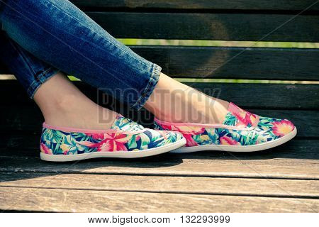 girl feet in lightweight summer shoes on wooden bench