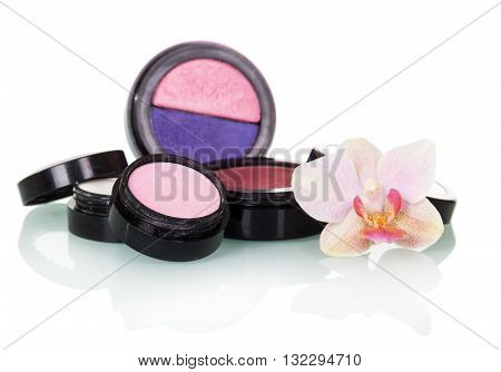 Professional Makeup: eyeshadow, blush and orchid flower isolated on white background.