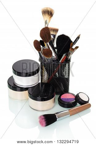 Cosmetic brushes for a make-up jars of creams, eye shadow and blusher isolated on white background.