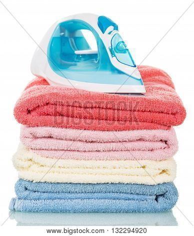 Steam iron and ironing colored towels isolated on white background.