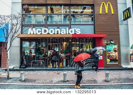 Tokyo Japan - February 26 2015: People passes on the pavement in front of McDonald's restaurant in Tokyo