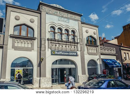 Mostar Bosnia and Herzegovina - August 25 2015. Muslim woman walks in front of Raiffeisen Bank building in Mostar