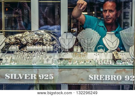 Mostar Bosnia and Herzegovina - August 25 2015. Seller shows some pieces of silver in shop in Mostar