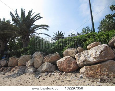 Rocks on the beach, near the palmtrees.