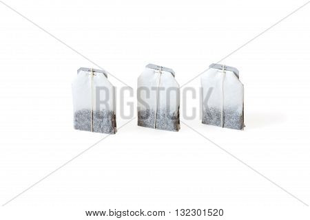 Three unused teabags in a row isolated on white background