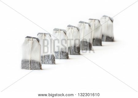 Seven unused teabags in a row isolated on white background