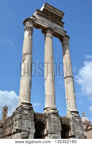 Ruins of the ancient Temple of Castor and Pollux (Dioskouri) in Roman Forum in the center of Rome with Capitol Tower and baroque dome