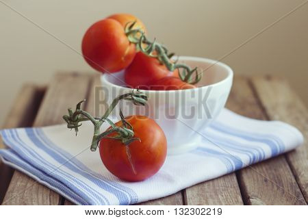 Tomatoes in white bowl on kitchen towel on wooden table