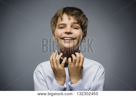Happy boy. Closeup Portrait of handsome teen in casual shirt smiling while standing against grey background.