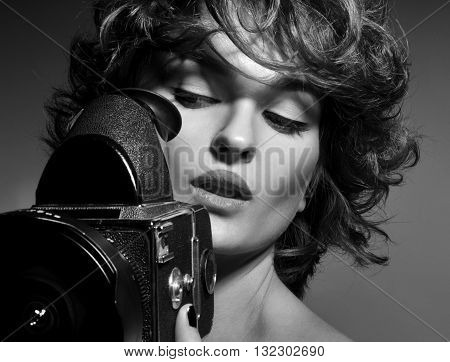 Black and white photo of beautiful woman with vintage photo camera