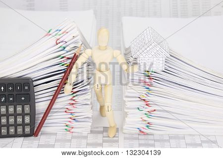 Wooden Dummy Holding House And Pencil Between Dual Overload Document