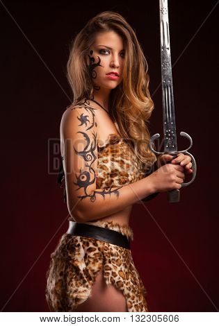 Portrait of a beautiful young girl with knife and tatoo on face. Warrior girl.