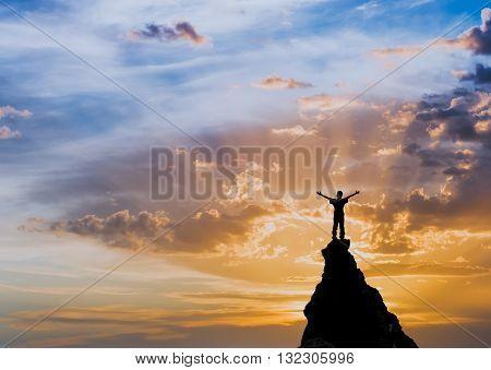 man on  top of rock meeting sun