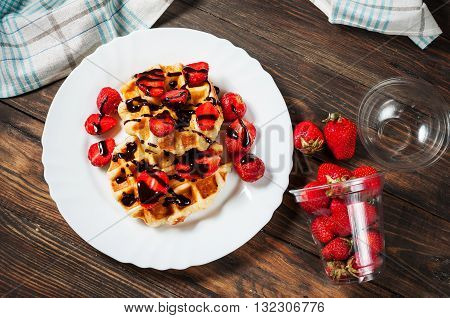 healthy breakfast waffle with strawberry and chocolate syrup on top.