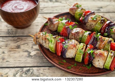 Barbecued marinated turkey or chicken meat shish kebab skewers with ketchup sauce, chopped parsley and tomatoes on rustic wooden table background. Traditional barbecue grill food