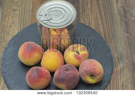 canned peaches, fresh peaches around the can