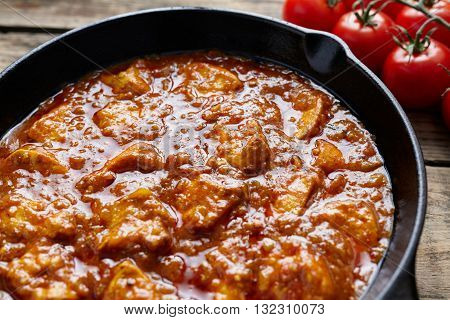 Tikka masala traditional Asian chicken meat with butter spicy food with tomatoes in cast iron skillet on vintage wooden background