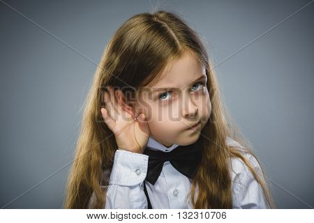 Curious Disappointed girl listens. Closeup portrait child hearing something, parents talk, hand to ear gesture isolated grey background. Human face expression, emotion, body language, life perception.
