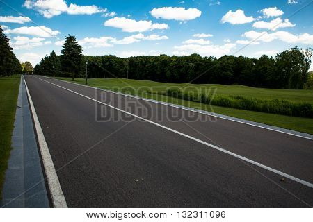Road panorama on summer evening. Carefree driving on a bright sunny day. Image of wide open prairie with paved highway stretching out as far as eye can see.