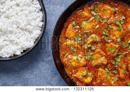 Chicken tikka masala national Indian spicy meat food with butter and rice in cast iron skillet